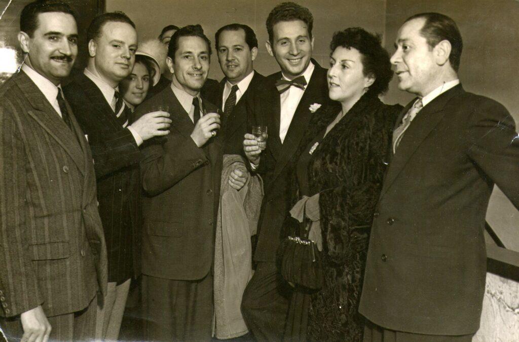 Charles Trenet rodeado de personal de la emisora durante un ágape después de su debut. 1948. LR1