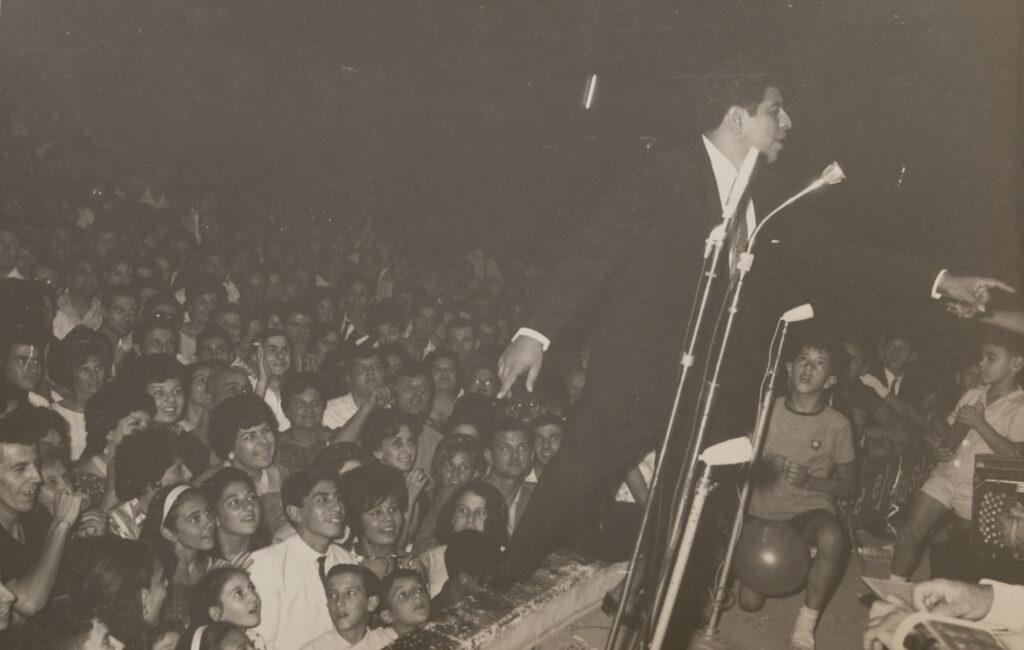 Cantor en escenario y su público